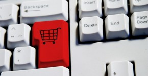 Computer Keyboard from a desktop computer with the enter key highlighted in Red with a large shopping cart on it