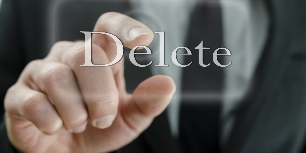 Businessman touching Delete button on a virtual screen.